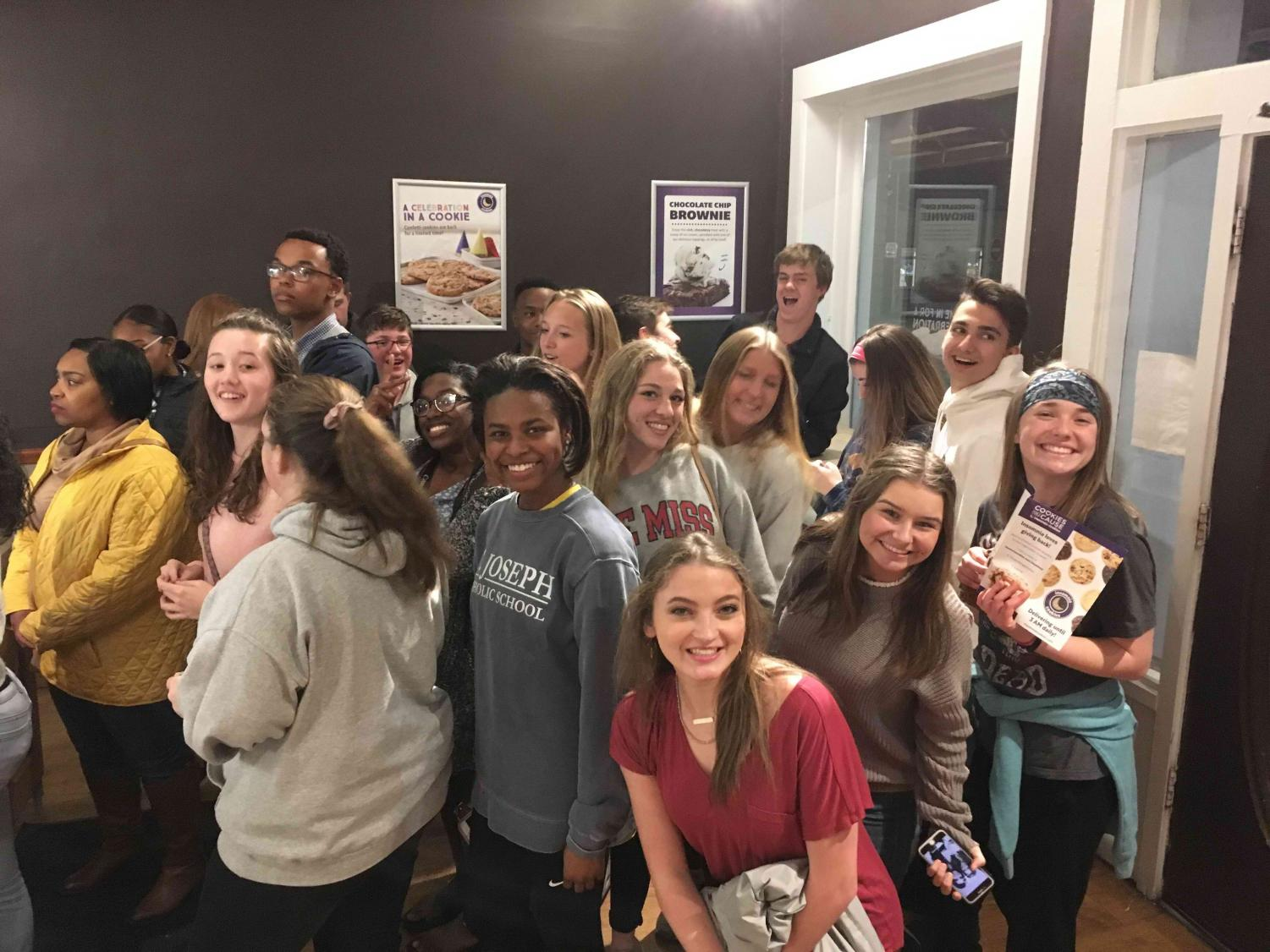 St. Joseph Catholic School journalism students stop by Insomnia cookie store on the Square in Oxford on Sunday, March 31, 2019, after eating dinner at Gus' Famous Fried Chicken.