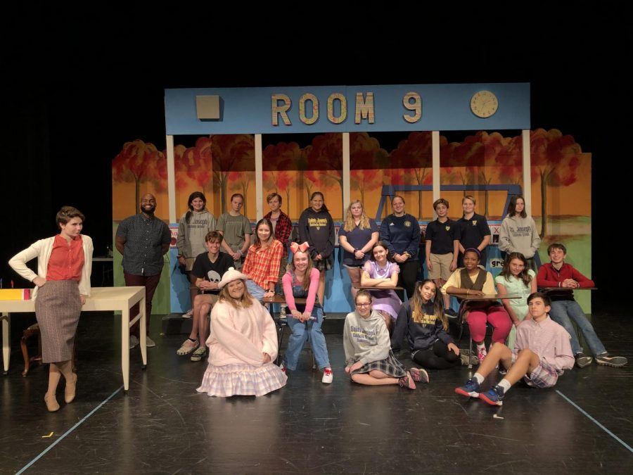 The+cast+crew+of+the+St.+Joseph+Catholic+School+stage+production+of+%E2%80%9CJunie+B.+Jones+is+NOT+a+Crook.%E2%80%9D+Back+row+from+left%3A+Mr.+Madison+Upendo%2C+the+St.+Joe+theater+teacher+and+play%E2%80%99s+director%3B+Loria+Williams%3B+Ava+Schuetzle%3B+Anna+Grace+Starnes%3B+Anna+Veston+Deer%3B+Abigail+Hardeman%3B+Molly+Moody%3B+Turner+Brown%3B+Connor+Odom%3B+and+Addie+Welshans.+Second+row+sitting+in+desks+from+left%2C+Anderson+Nixon%2C+Annalise+Rome%2C+Hannah+Dear%2C+Georgia+Conrad%2C+Natalia+Igwebuike+and+Andrew+Bain.+Sitting+on+the+floor%2C+Mary+Kathryn+David%2C+Madalyn+Weisenberger%2C+Iliana+Ramos%2C+Meredith+Morrow+and+Heath+Dodson.+Leaning+against+the+desk+on+the+far+left+is+Kim+Kaiser.+