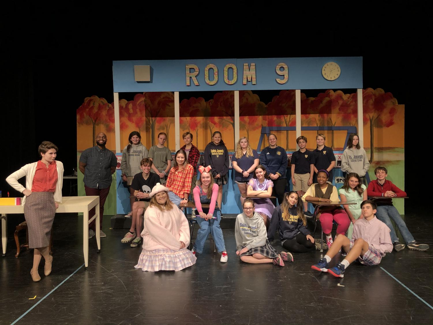 """The cast crew of the St. Joseph Catholic School stage production of """"Junie B. Jones is NOT a Crook."""" Back row from left: Mr. Madison Upendo, the St. Joe theater teacher and play's director; Loria Williams; Ava Schuetzle; Anna Grace Starnes; Anna Veston Deer; Abigail Hardeman; Molly Moody; Turner Brown; Connor Odom; and Addie Welshans. Second row sitting in desks from left, Anderson Nixon, Annalise Rome, Hannah Dear, Georgia Conrad, Natalia Igwebuike and Andrew Bain. Sitting on the floor, Mary Kathryn David, Madalyn Weisenberger, Iliana Ramos, Meredith Morrow and Heath Dodson. Leaning against the desk on the far left is Kim Kaiser."""