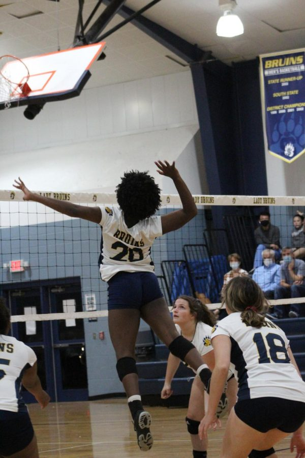 Senior Grace Goodloe spikes the ball during a home volleyball game.
